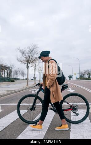 Young man with bicycle crossing a street in the city - Stock Photo