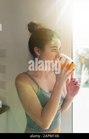 Female teenager drinking juice and looking out of the window - Stock Photo