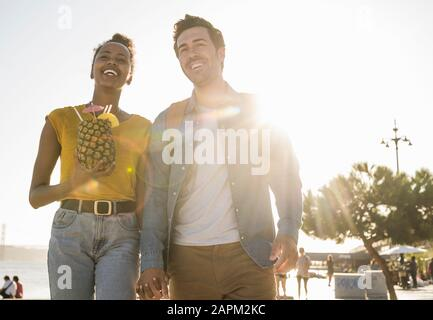 Happy young couple walking at the waterfront at sunset, Lisbon, Portugal Stock Photo