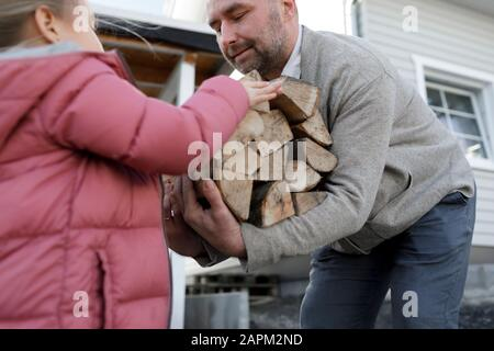 Man carrying firewood, daughter giving him wood - Stock Photo