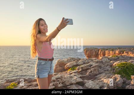 Young woman standing on cliff at the sea, using smartphone, taking selfie - Stock Photo