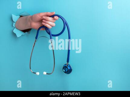 Stethoscope in a female hand on a blue background with a hole, medical concept. Horizontal orientation, copy space - Stock Photo