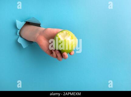 A woman's hand holds a bitten apple through a hole in the paper on a blue background. Copy space