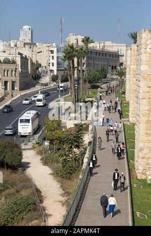 Jerusalem street scene with pedestrians walking along the outside of the old city wall in the Mamilla neighborhood.  View from above. - Stock Photo