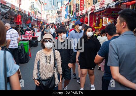 23.01.2020, Singapore, Republic of Singapore, Asia - Pedestrians cover their faces with surgical masks at a street bazaar in Chinatown.