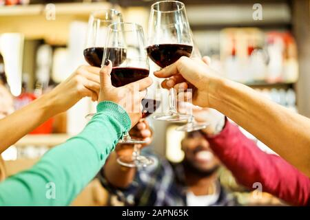 Group of students cheering with red wine at aperitif dinner bar - Young cheerful people toasting drinks in restaurant - Good and positive mood with fr - Stock Photo