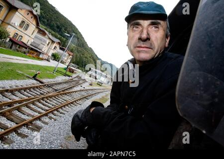 Most na Soči, Slovenia, October 4, 2008: An engine driver looks out from a 1944 Henschel & Son German steam engine pulling an old museum train on the Bohinj railway line (Transalpina) that was built from 1900 to 1906 as the shortest connection of the Austro-Hungarian Empire with the Adriatic Sea in Trieste (Italy). - Stock Photo