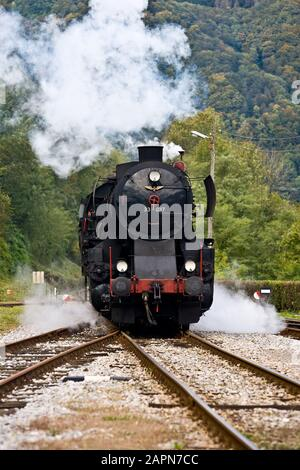 Most na Soči, Slovenia, October 4, 2008: A 1944 German Henschel & Son steam engine pulling an old museum train waits at the Most na Soči train station during a ride on a hundred-year-old Bohinj railway line (Transalpina) that was built from 1900 to 1906 as the shortest connection of the Austro-Hungarian Empire with the Adriatic Sea in Trieste (Italy). - Stock Photo