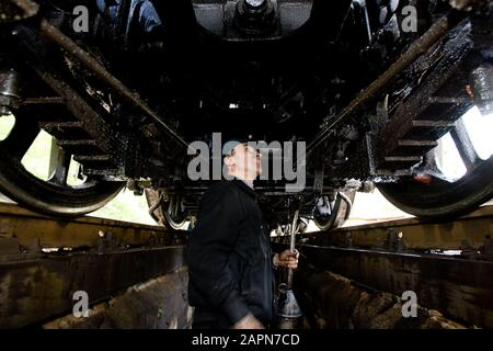 Most na Soči, Slovenia, October 4, 2008: An engine driver inspects the undercarriage of a 1944 Henschel & Son German steam engine at the Most na Soči train station. The locomotive is one of two that pull an old museum train on the Bohinj railway line (Transalpina) built from 1900 to 1906 as the shortest connection of the Austro-Hungarian Empire with the Adriatic Sea in Trieste (Italy). - Stock Photo
