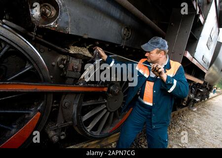 Most na Soči, Slovenia, October 4, 2008: A man cleans a 1944 Henschel & Son German steam engine at the Most na Soči train station. The locomotive is one of two that pull an old museum train on the Bohinj railway line (Transalpina) built from 1900 to 1906 as the shortest connection of the Austro-Hungarian Empire with the Adriatic Sea in Trieste (Italy). - Stock Photo