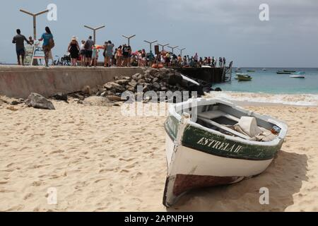 On the beach with traditional fisherman's boat in foreground with the daily fish market on the pier in the background in Santa Maria Sal, Cape Verde - Stock Photo