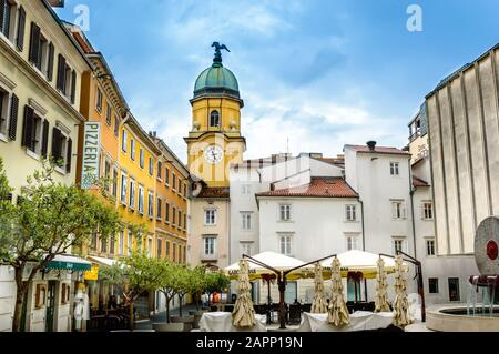 Rijeka, Croatia - May 19, 2019: square behind yellow City Clock Tower with cafe tables, umbrellas and olive trees on a sunny day. Yellow buildings wit