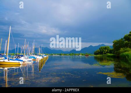 A small harbor on the Chiemsee lake (Bavaria, Germany) on a calm, beautiful and sunny summer day. Several sailboats are parked near a pier. - Stock Photo