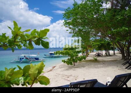 A small island in the Philippines archipelago. There are two paraw boats parked near the sandy beach. The ocean is calm, it's sunny and warm. - Stock Photo