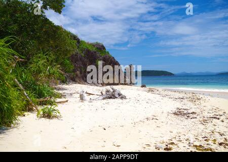 A small, deserted island in the Philippines archipelago. The island has a beautiful sandy beach and a patch of palm trees growing near big jagged rock - Stock Photo