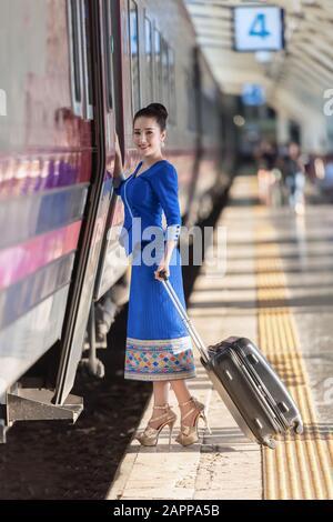 Traveler girl walking and waits train on railway platform - Stock Photo