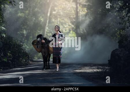 Asian woman worker with her donkey in forest countryside of Thailand - Stock Photo