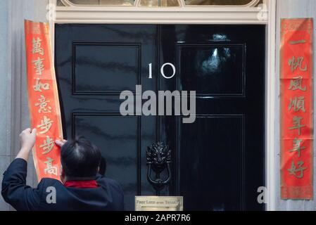 London, UK. 24th Jan, 2020. A man pastes couplets outside 10 Downing Street in London, Britain, Jan. 24, 2020, to celebrate the Chinese Lunar New Year. Credit: Ray Tang/Xinhua/Alamy Live News - Stock Photo