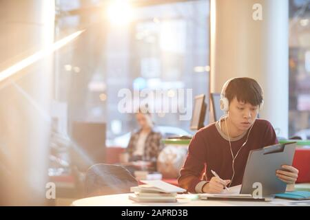 Asian young man in headphones sitting at the table with clipboard and making notes in notebook he working in the library