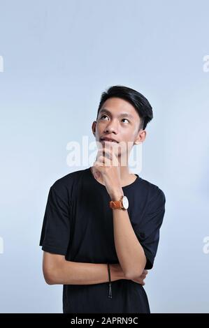 Handsome young asian boy wearing black t-shirt and wristwatch with hand on chin thinking about question, pensive expression. Smiling with thoughtful f - Stock Photo