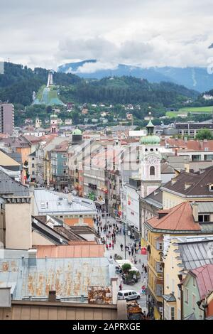 Innsbruck, Austria - July 29th 2019: View of a main street in the old part of the city of Innsbruck in Tirol, Austria. Mountains in the background. - Stock Photo