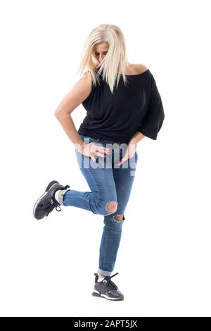Vitality concept of playful middle aged woman in fifties posing and standing on one leg. Full body length isolated on white background.
