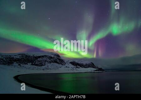 Intense northern lights, Aurora Borealis at a bay near Honningsvag and the Nordkapp, North Cape, Finnmark, Norway, Europe - Stock Photo