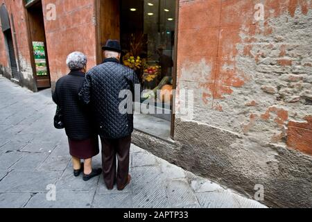 Siena, Italy, October 27, 2008 - An elderly couple look at a shop window. - Stock Photo