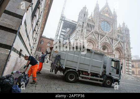 Siena, Italy, October 27, 2008 - Sanitary workers pick up waste in front of the Siena Cathedral (Duomo di Siena). - Stock Photo