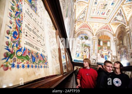 Siena, Italy, October 27, 2008: A closeup of a manuscript in the Piccolomini library of the Siena Cathedral (Duomo di Siena) with visitors. - Stock Photo