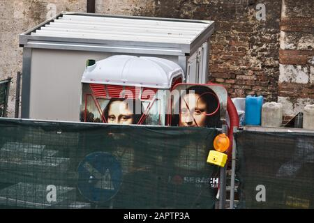 Siena, Italy, October 27, 2008: The famous Mona Lisa on a painted portable toilet peers over a work fence of a construction site in Siena, Italy. - Stock Photo
