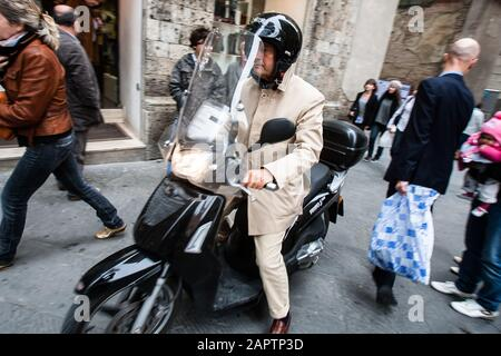 Siena, Italy, October 27, 2008: A man in a suit rides a scooter through the crowded streets of Siena, Italy. - Stock Photo
