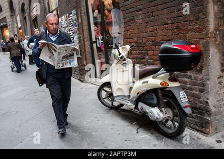 Siena, Italy, October 27, 2008: A man reading a newspaper walks pass a parked scooter in the street in Siena, Italy. - Stock Photo