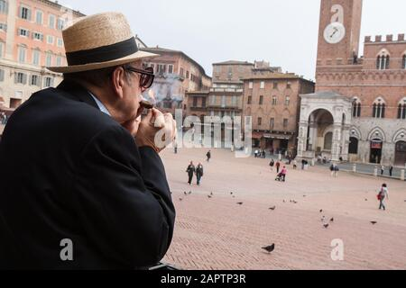 Siena, Italy, October 27, 2008: A man lights a cigar in the Piazza del Campo in Siena, Italy. - Stock Photo