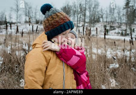 siblings playing and cuddling outside whilst playing in the snow - Stock Photo