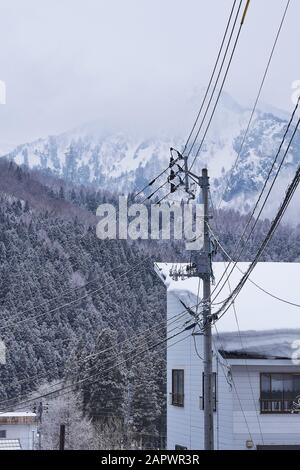 Power lines and snow covered building in the foreground, with snowy trees and mountains in the background. - Stock Photo