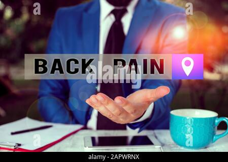 Writing note showing Back Pain. Business concept for Soreness of the bones felt at the lower back portion of the body Man in front of table. Mobile ph - Stock Photo