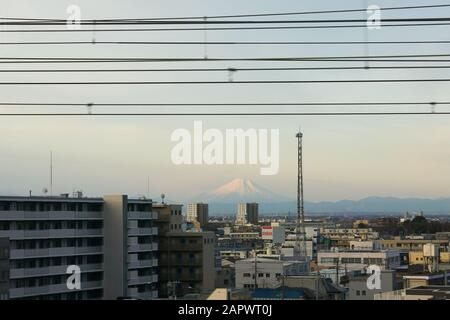 A snowy Mount Fuji (Mt. Fuji) towers in the distance over a city skyline in Japan. - Stock Photo