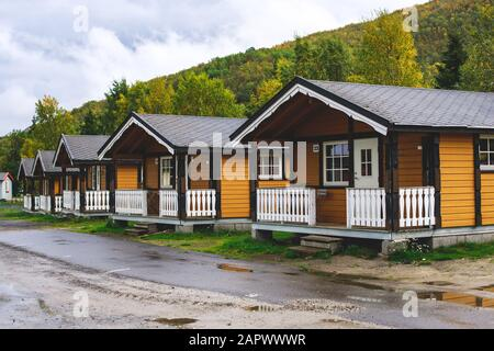 View of Classical Norwegian Camping site with traditional wooden red cottages, Northern Norway - Stock Photo