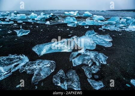 Icebergs on Diamond Beach in Iceland. Frozen ice on black sand beach known as Diamond Beach flows from Jokulsarlon beautiful Glacial Lagoon in Vatnajo - Stock Photo