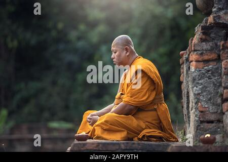 Buddhist monk meditation in temple - Stock Photo