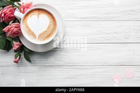 A cup of coffee with heart pattern  and roses on a white wooden background - Stock Photo