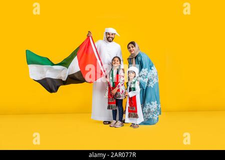 Middle eastern family with traditional emirates dresses posing in a photographic studio - Concepts about lifestyle, happiness and family relationship - Stock Photo