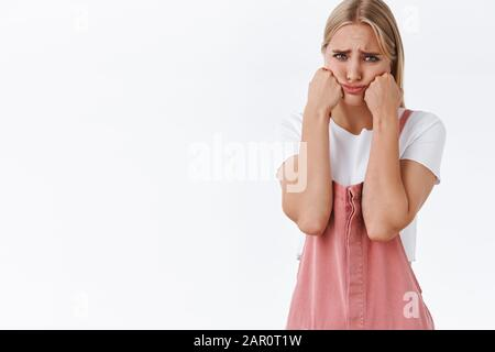Upset childish and silly cute blond girlfriend, whining feeling bad and offended, crying, squeeze cheeks looking uneasy and lonely, pouting, sulking - Stock Photo