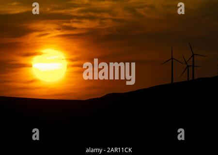 sunset over mountains with wind turbines in county donegal ireland eco energy and renewables concept - Stock Photo