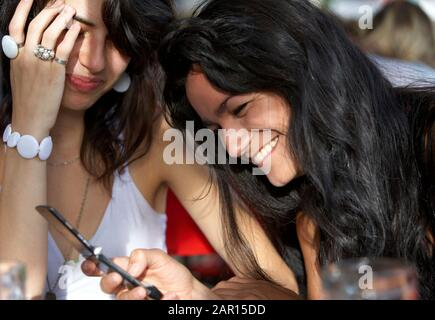 two young hispanic 20s women laughing over a text on screen app message mobile phone buenos aires argentina  Model released image