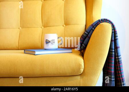 Cup of tea and blue book on yellow coach with blanket. Still life details in home interior of living room. Cozy home interior, home comfort concept - Stock Photo