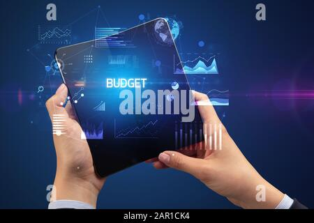 Businessman holding a foldable smartphone with BUDGET inscription, successful business concept - Stock Photo