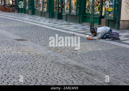 PRAGUE, CZECH REPUBLIC – JANUARY 22 2020: Lone man begging on the streets of old town - Stock Photo