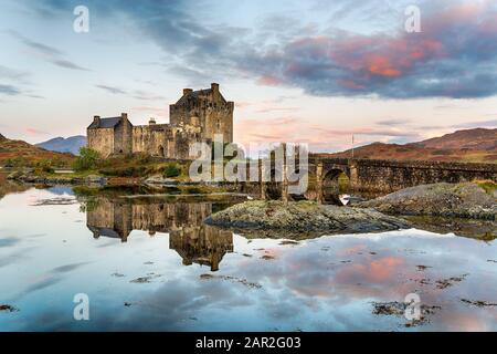 Sunrise over Eilean Donan castle reflected in the still waters of the loch at Dornie in the Highlands of Scotland - Stock Photo